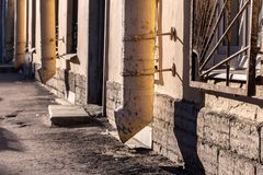 Empty street and rhythm downpipes. Old yellow drainpipes on a building wall in the morning sun. city street photography. empty street and rhythm downpipes stock photos