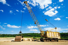 Old yellow excavator under blue sky. Old yellow excavator moving sand under blue sky Royalty Free Stock Images