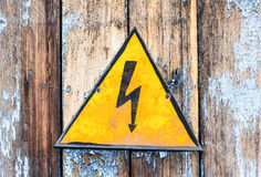 Old yellow high voltage caution sign Royalty Free Stock Images