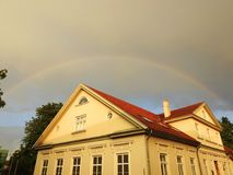 Old yellow home and rainbow, Latvia royalty free stock photography