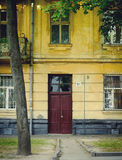 Old yellow house facade with red door Royalty Free Stock Photography