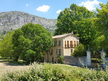 An old Yellow house in the French Provence Alps surrounded by trees and a huge mountain in the background. An old style, French villa with a typical French Royalty Free Stock Photo