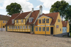 Old yellow houses in street with cobblestones. Old traditional Danish yellow half-timbered houses with casement windows in street with  cobblestones in Roskilde Stock Image