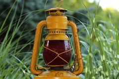 Old Yellow Lantern With Red Globe. Antique Yellow Lantern With Red Globe With Ornamental Green Grass In Background royalty free stock photography