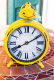 Old yellow mechanical alarm clock on stone table Royalty Free Stock Photography