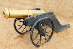 Old yellow metal cannon with black wheels on sand Royalty Free Stock Image
