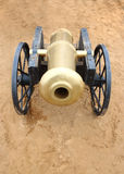Old yellow metal cannon with black wheels on sand outdoor Stock Image