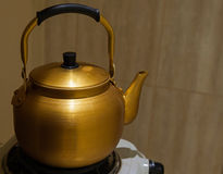 Old yellow metal teapot on the stove Stock Images