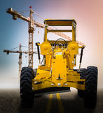 Old yellow motor grader on the road Royalty Free Stock Images
