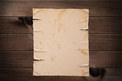 Old yellow paper on wooden wall. Stock Image