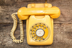 Old yellow phone with dust and scratches, still life. Royalty Free Stock Image