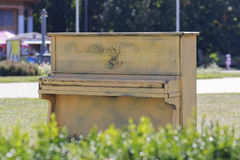 Old yellow piano stands in the park Stock Photo