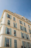 Old Yellow Plaster French Hotel with Green Shutters Royalty Free Stock Image
