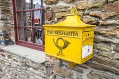 Old yellow post mailbox in Germany Royalty Free Stock Photo