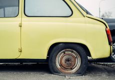 Old yellow retro car. With a punctured broken wheel stock photography