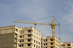 Old yellow rusted crane near the unfinished high-rise building Stock Photos