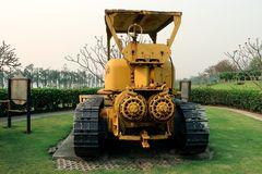 Old yellow rusty crawler tractor in the field. Old crawler tractor on green garden stock photos