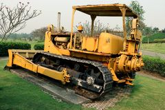 Old yellow rusty crawler tractor in the field. Old crawler tractor on green garden royalty free stock photos