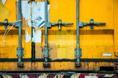 Old yellow shipping container door. Backgrounds Stock Photos