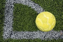 Old football ball at corner. Old yellow soccer ball, Football at artificial grass corner line in soccer stadium with copy space for text background. Outdoor Stock Photo