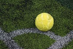 Old yellow soccer ball on football grass. Old yellow soccer ball, Football on artificial grass corner line in soccer stadium with copy space for text background Stock Photo