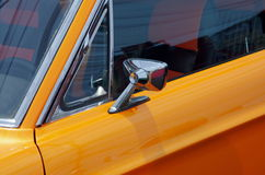 Old yellow sports car. Lateral rear-view mirror on a old yellow sports car Stock Photography
