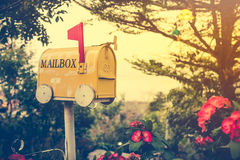 Old yellow stained metal mailbox has red flag raised up. To indicate mail has arrived. Outdoor on summer day with bright sunlight at sunset. Vintage effect tone Royalty Free Stock Photos