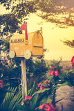 Old yellow stained metal mailbox has red flag raised up to indicate mail has arrived. Royalty Free Stock Photography