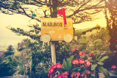 Old yellow stained metal mailbox has red flag raised up to indicate mail has arrived. Royalty Free Stock Photo