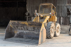Old yellow tractor parks in factory. With rusric galvanize metal in the background Stock Images