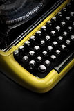 Old yellow typewriter in shadow Stock Photography