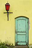 Old yellow wall with green door Stock Images