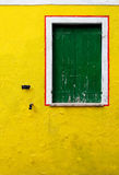 An old yellow wall with a green window Stock Photos