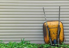 Old yellow wheel barrow leaning against a shed royalty free stock photo