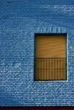 Old yellow window in light blue wall Royalty Free Stock Photo