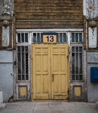 Old, yellow, wooden door with the number 13. Royalty Free Stock Photography