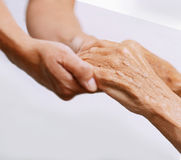 Old and Young. Holding hands on light background: black and white version royalty free stock photography