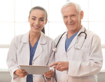Old and young doctors. Handsome old doctor and beautiful young female doctor in white medical coats are using a digital tablet, looking a camera and smiling Royalty Free Stock Photo