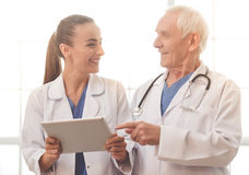 Old and young doctors. Handsome old doctor and beautiful young female doctor in white medical coats are using a digital tablet, talking and smiling Stock Image
