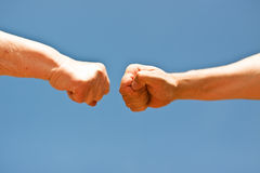 Old and young fists punching each other Stock Image