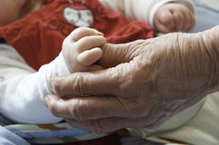 Old and young hand. Baby hand in grandmother hand Royalty Free Stock Photos