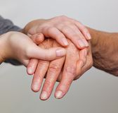 Old and young hand with walking stick Stock Image