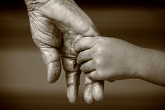 Old and young hands. An old woman and a kid holding hands together stock photography