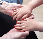 Old and young hands. Little girl is laying her hands in her grandmothers old hands Stock Photo