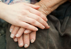 Old and young hands. Hands of the old woman - 84 years covered with young hands stock image