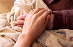 Old and Young Hands. On Brown Blanket stock photos