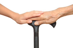 Old And Young Hands. Holding Onto A Walking Stick stock images
