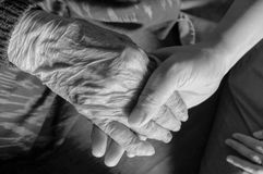 Old and young hands check hand black and white Stock Photos