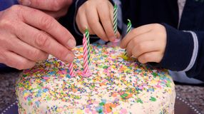 Old & young hands put candles on a cake Royalty Free Stock Photos