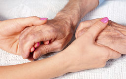 Old and young holding hands on light background, closeup. Care is at home of elderly. Old and young holding hands on lwhite background, closeup. Care is at home Royalty Free Stock Photo